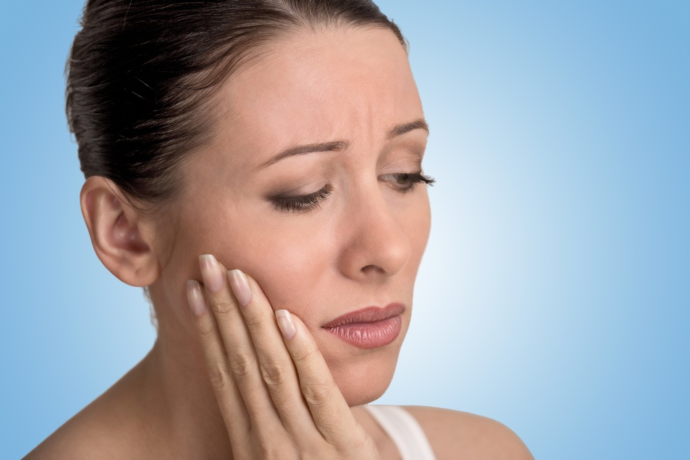 Closeup portrait young woman with sensitive tooth ache crown problem about to cry from pain touching outside mouth with hand isolated blue background. Negative emotion facial expression feeling.jpeg